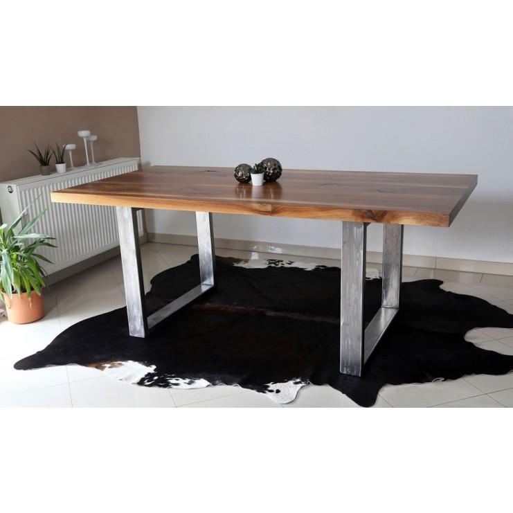 Die strukturstarke Tischplatte aus Nussbaum (lackiert) wird von einem Tischgestell aus Stahl gehalten. Bei einer Länge von 1,90 Metern haben so ganz bequem sechs Personen Platz.